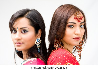 Two beautiful Bengali brides in colorful dresses, isolated
