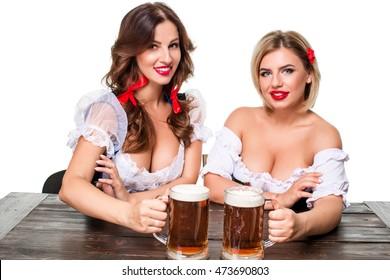 Two beautiful blond and brunette girls of oktoberfest beer stein