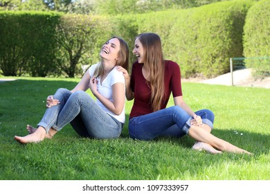 Two beautiful blond women with naked feet sitting on grass and having fun together