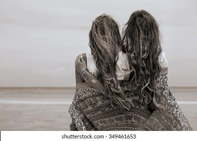 Two beautiful boho girls looking at sea. Back view