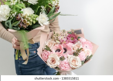 Two Beautiful bouquets of mixed flowers in womans hands. the work of the florist at a flower shop. Delicate Pastel color. Fresh cut flower. Green and pink color
