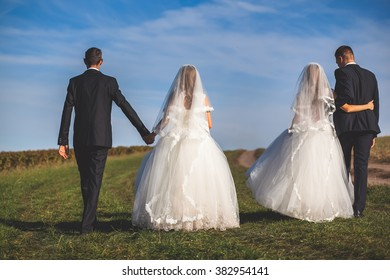 Two beautiful brides in field couples