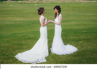 Two beautiful brides holding hands on the green field of the golf club