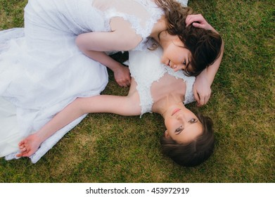Two beautiful brides lying on the green field of the golf club