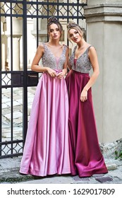 Two beautiful bridesmaids girls blonde and brunette ladies wearing elegant full length purple violet lilac lavender satin bridesmaid dress with silver sequined camisole top. European old town location