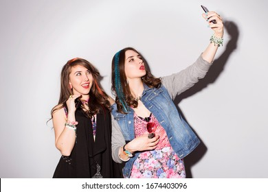 Two beautiful brunette women (girls) teenagers spend time together having fun, make funny faces, making selfie. Retro outfit: blue tights, jeans jacket, shorts in sequins, and colored strand of hair