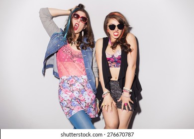 Two beautiful brunette women (girls) teenagers spend time together having fun, make funny faces. Retro outfit: bright blue tights, jeans jacket, shorts in sequins, and colored strand of hair