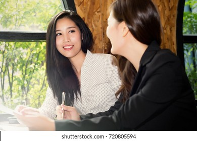 Two beautiful Business woman Asian working together in office, Consulting jobs, Making great decisions, co-workers discussing