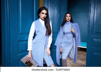 Two beautiful business woman lady style perfect body shape brunette hair wear blue color dress coat jacket elegance casual style glamour fashion bag accessory shoes jewelry interior door luxury party.
