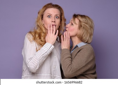 Two beautiful caucasian mature women telling secret on a colored background. The latest news and gossip concept.