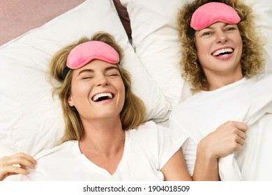 Two beautiful and cheerful girls with a pink blindfolds lying and relaxing in bed