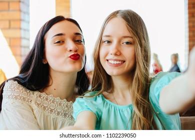 Two beautiful, cheerful, smiling girls do selfie.
