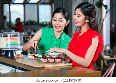 Two beautiful and cheerful young women choosing cupcakes in the interior of a trendy coffee shop with delicious confections for sale