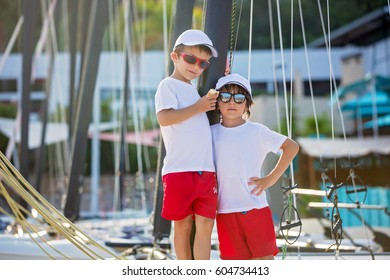 Two beautiful children, boy brothers, standing on a boat, smiling, summertime on sunset
