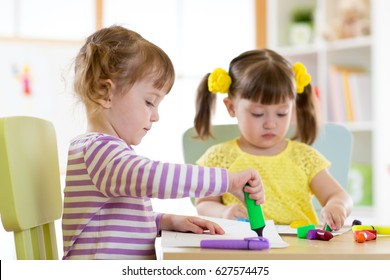 Two beautiful children girls drawing in kindergarten or preschool