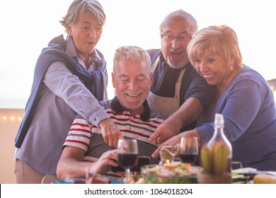 two beautiful couples doing picture with mobile phone during dinner on the rooftop patio outdoor in vacation. lifestyle for retired happy concept