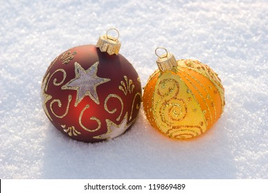 Two beautiful decorative spheres on a white snow.