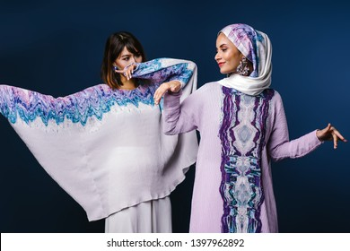 Two beautiful, elegant and attractive Malay Asian Muslim women in festive and traditional festive clothing for Raya / Eid / Ramadan. They are smiling and dancing. One is wearing a hijab headscarf.
