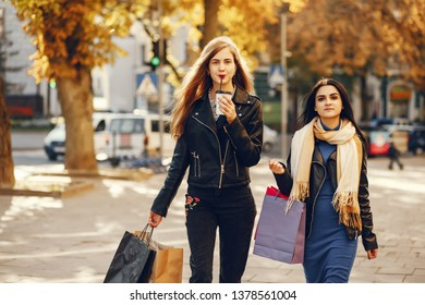 Two beautiful elegant girls walking around the city with shopping bags