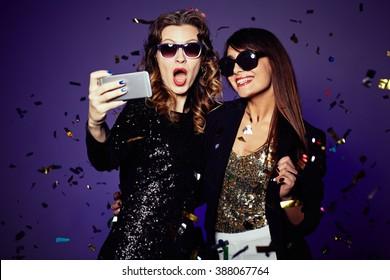 Two beautiful elegant women making selfie
