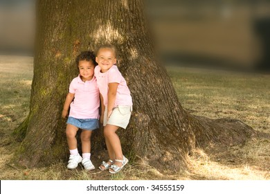 Two beautiful ethnic sisters little girls in the park posing against the base of a large tree trunk.