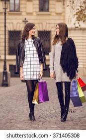 two beautiful fashion models posing outside with shopping bags; two young women laughing, having fun