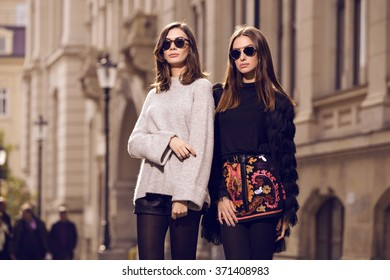 two beautiful fashion models posing outside wearing a grey sweater with leather shorts, studded ankle boots and a fringed cardigan, black T-shirt, embroidered A-line skirt  heeled ankle boots