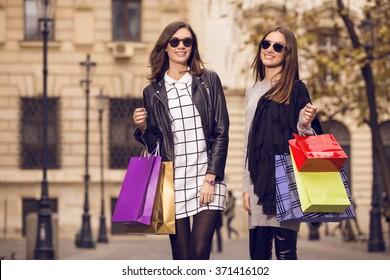 two beautiful fashion models posing outside with shopping bags; two young women laughing, having fun, wearing sunglasses