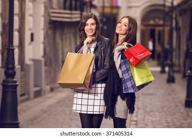 two beautiful fashion models with shopping bags, posing outside; two young women laughing, having fun