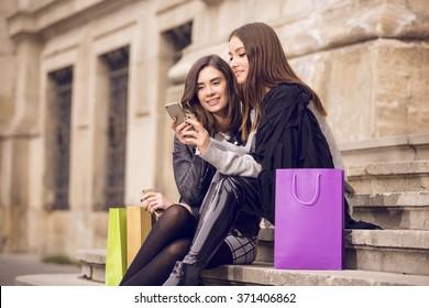 two beautiful fashion models with shopping bags; two young women laughing, having fun, checking the phone, or taking a selfie; shopping break