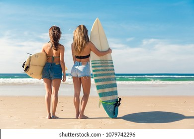 Two beautiful female friends at the beach holding her surfboards while looking to the ocean