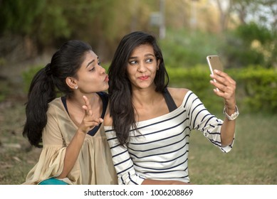 Two beautiful female friends taking selfie with smartphone in outdoors.