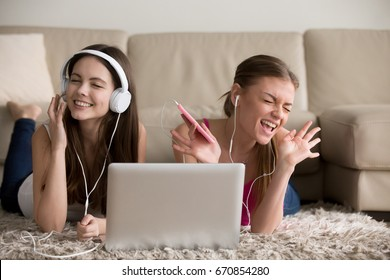 Two beautiful female music lovers in headphones enjoying popular musical compositions online with app on cellphone and laptop. Excited women friends singing songs and having fun while lying on floor