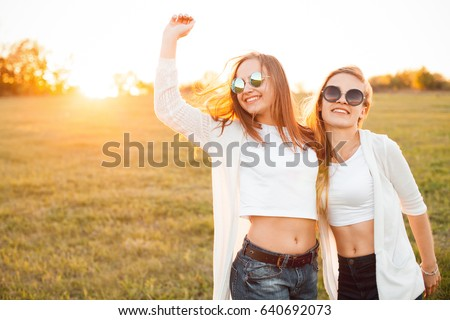 Two beautiful females are walking on a field at sunset. Best friends