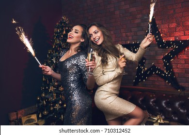 Two beautiful girl in confetti with champagne and sparkle. Funny and happy girl in a beautiful sexy dress. You are special, you are unique; may your  Merry Christmas!