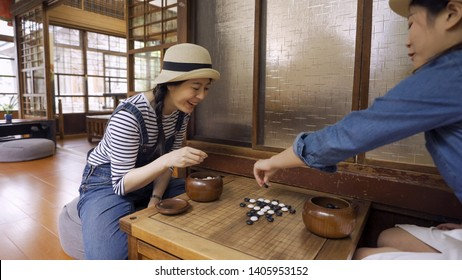 Two beautiful girl friends playing chess with japanese style house interior. young female travelers having fun together with igo go stones. attractive laughing women play chinese board game cheerful