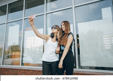 Two beautiful girl at the window wall with headphones