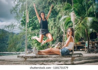 Two beautiful girlfriend enjoy a swing and drink coconut on the beach. Tropical travel holidays