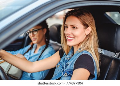 Two beautiful girlfriends driving in the car and smiling