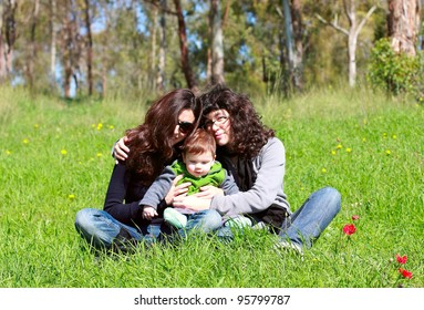two beautiful girls with a baby in the background of the spring forest