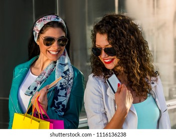 Two beautiful girls, closeup with bags and credit cards laughing