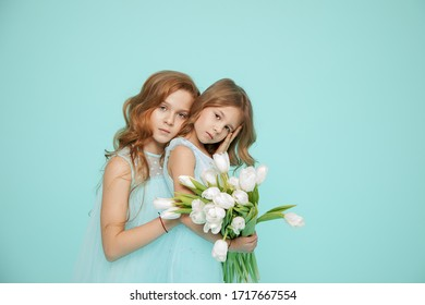 Two beautiful girls with curly locks of hair in dresses are embracing on a blue background. Photo. White Tulip. Hair salon. Psychology of relationships. Look at camera. Friendship, love, family, touc