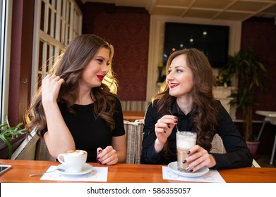 Two beautiful girls drinking coffee
