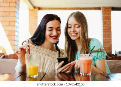 Two beautiful girls are drinking fresh fruit smoothies in a cafe.