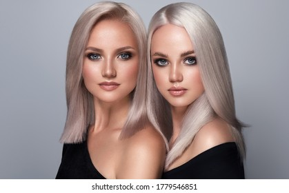Two beautiful girls with dyed hair in blond. Stylish hairstyle curls done in a beauty salon. Beauty, cosmetics and makeup