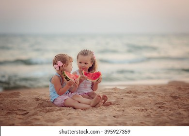 Two beautiful girls eating ripe watermelon on the beach