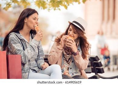 Two beautiful girls eating sandwich after shopping.