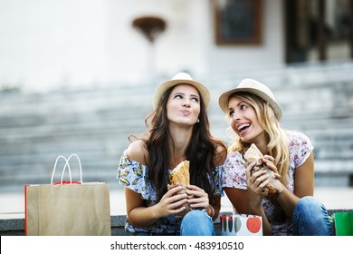 Two beautiful girls eating sandwiches and shopping.