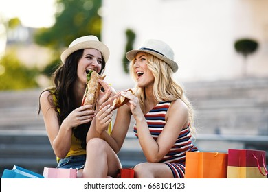 Two beautiful girls eating sandwiches after shopping.