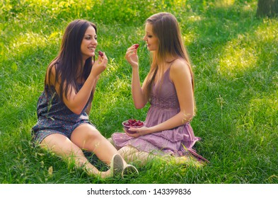 Two beautiful girls eating strawberries in the nature on sunny summer day.